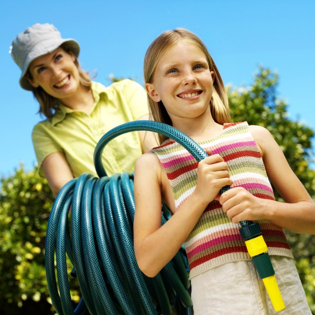 portrait of a mother and daughter holding a garden hose in the yard