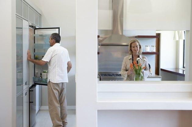 Couple in kitchen, man looking in fridge, woman arranging flowers