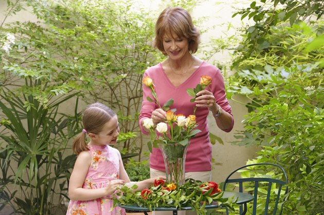 Grandmother and granddaughter (6-8) arranging flowers in vase, smiling