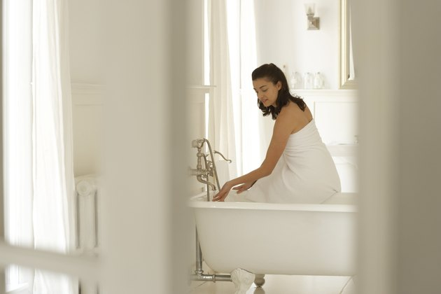 Young woman sitting on edge of bath, testing water with hand