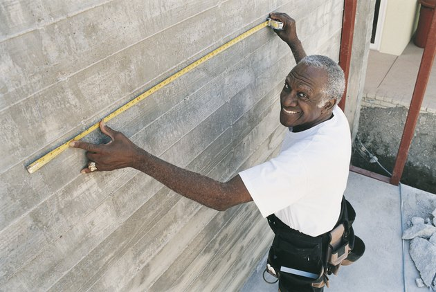 Elevated View of a Man Measuring a Wall With a Tape Measure