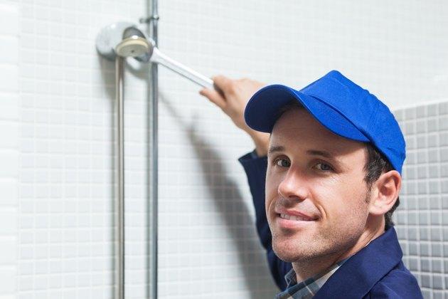 Cheerful plumber repairing shower head