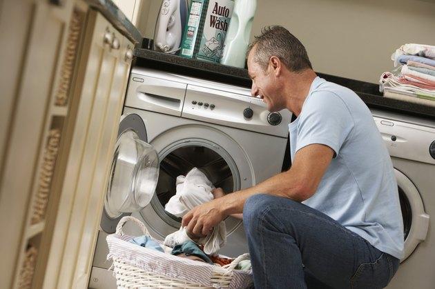Mature man loading washing machine, smiling