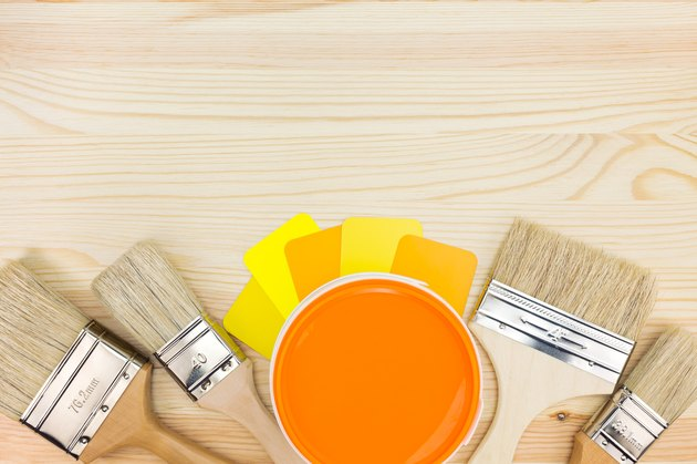 brushes, color guide and paint can on wooden background
