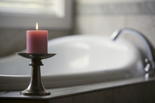 Pink candle burning beside bath tub in bathroom
