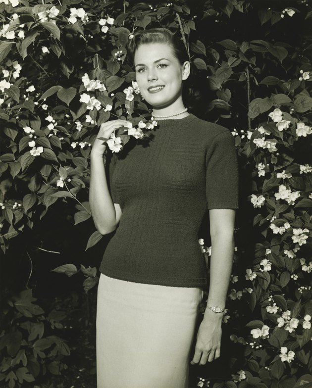 Woman posing at blooming jasmine bush, (B&W), (Portrait)