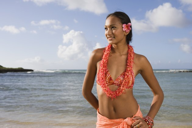Woman in lei and bikini by ocean