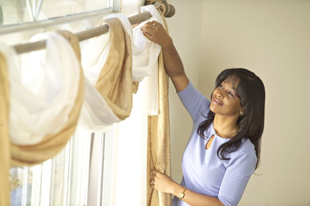 Woman Styling New Drapes in Living Room