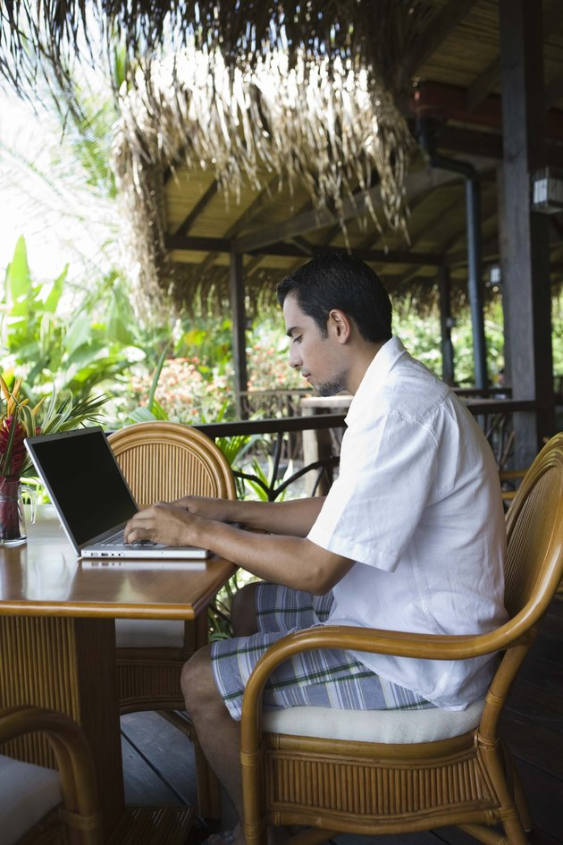Man working on laptop computer in tropical cafe