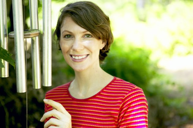 Woman smiling by wind chimes