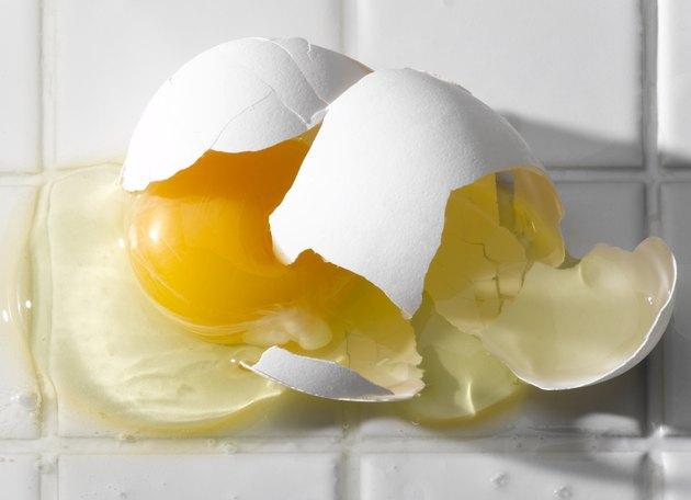 Broken egg on white tiles