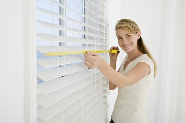 Woman measuring window blinds