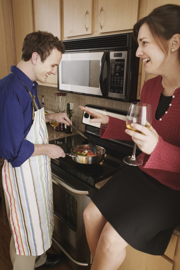 Couple drinking wine while preparing food