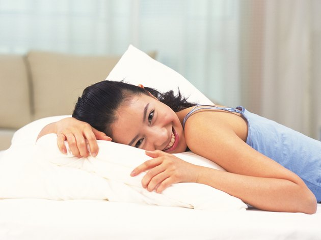 Woman smiling and lying on bed