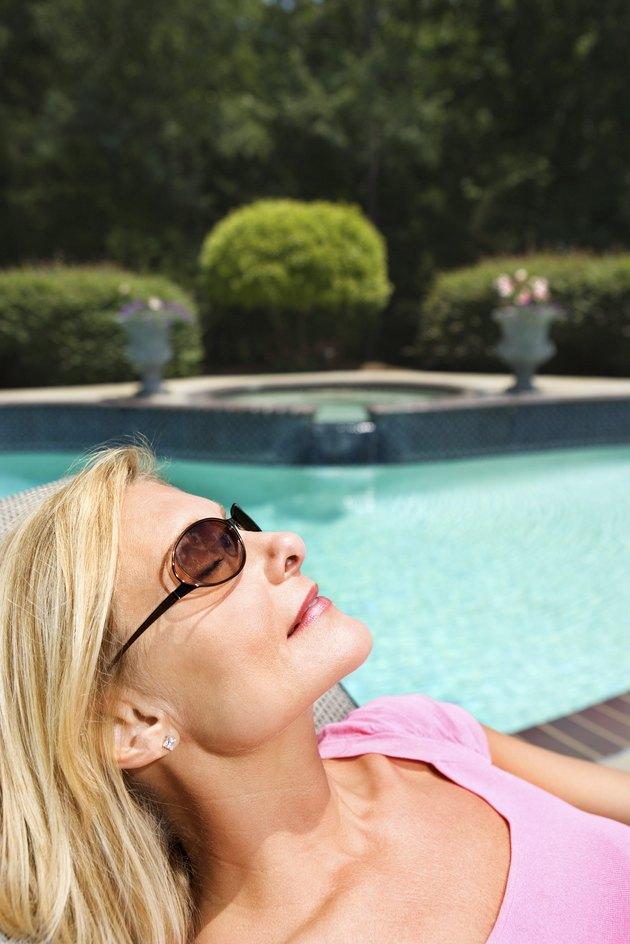 Woman sunbathing by pool