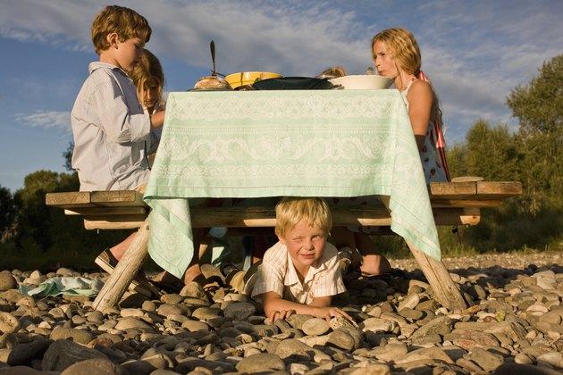 Boy hiding under outdoor table
