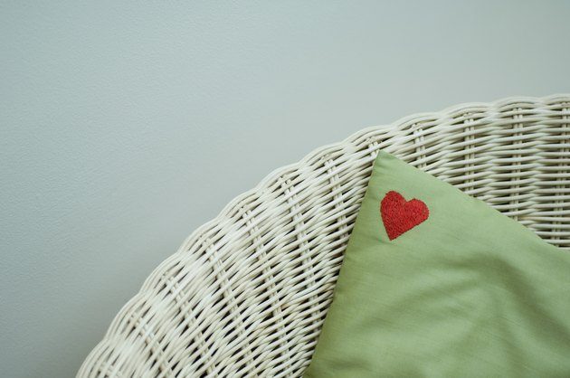 Red heart on corner of pillow in wicker chair