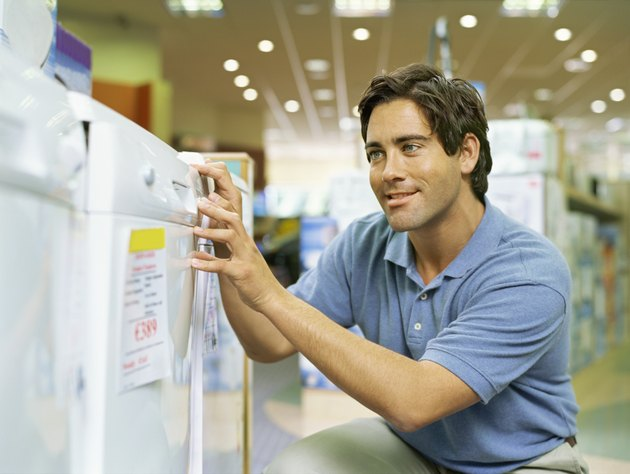 close-up of a young man looking at a refrigerator in an electronics store