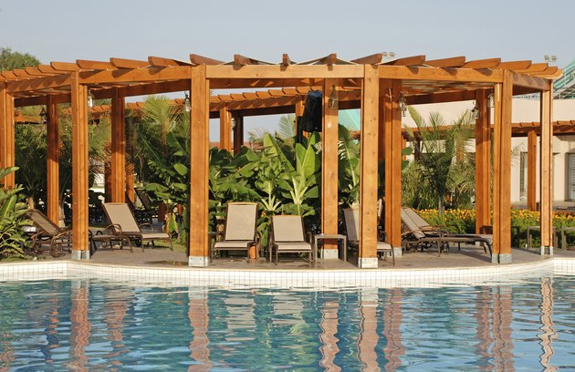 resort swimming pool, wood pergola and deck chairs