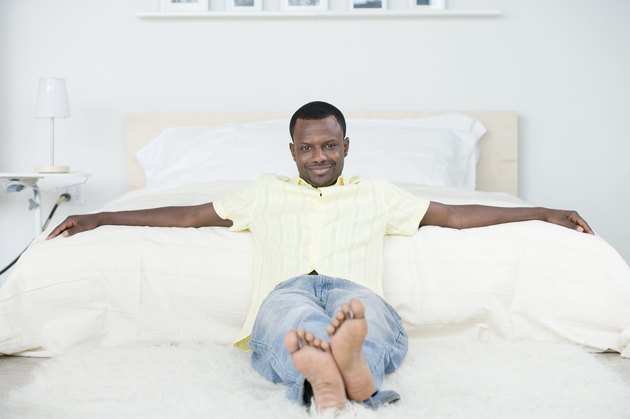 Man reclining against futon at home