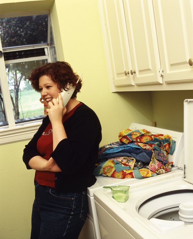 Woman talking on telephone in laundry room