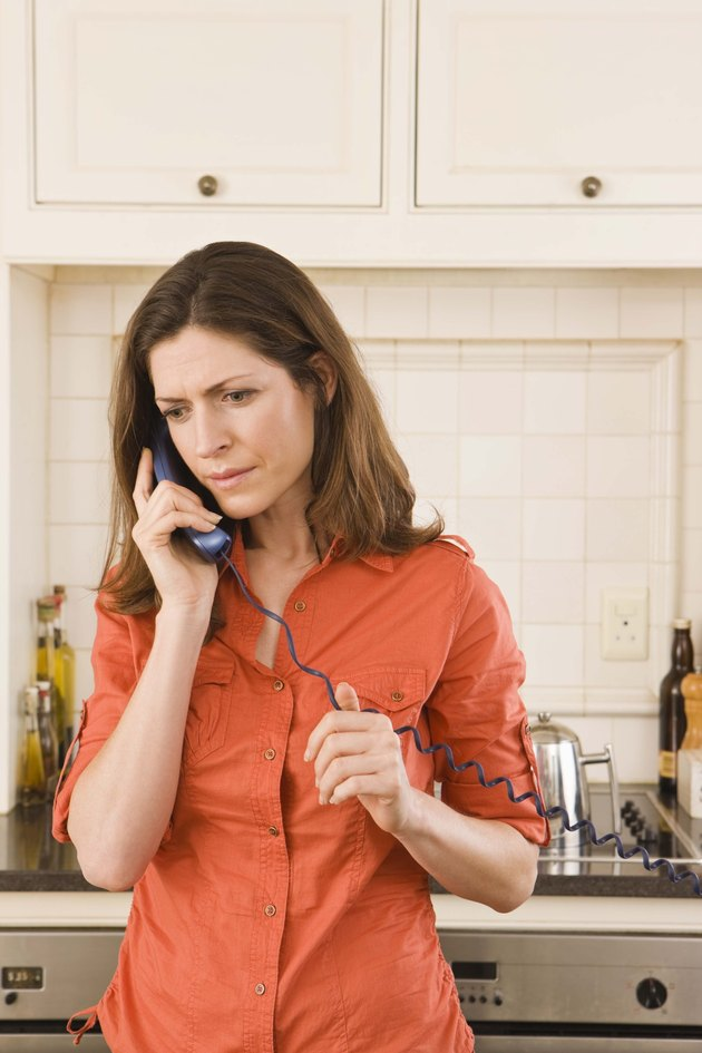 Worried woman in kitchen on telephone