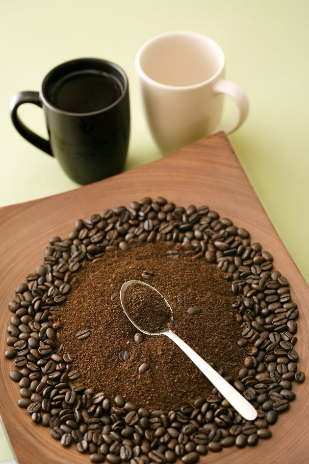 Spoon in pile of ground coffee and whole beans with mugs