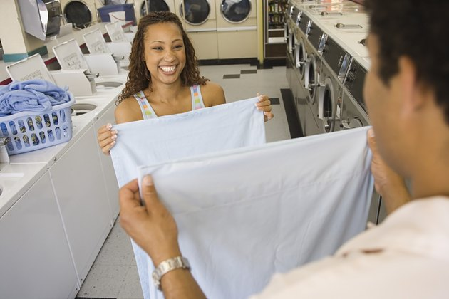 Couple folding sheets in launderette