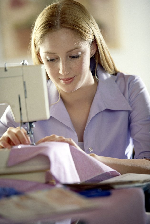 Teenage girl using sewing machine
