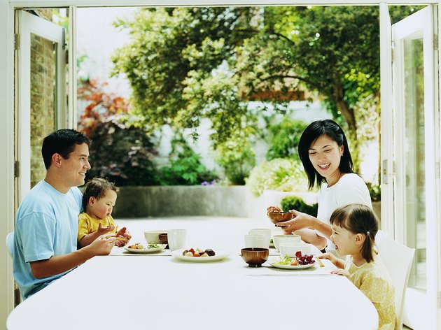 Family of Four Dining at a Table With French Windows Open Onto a Courtyard