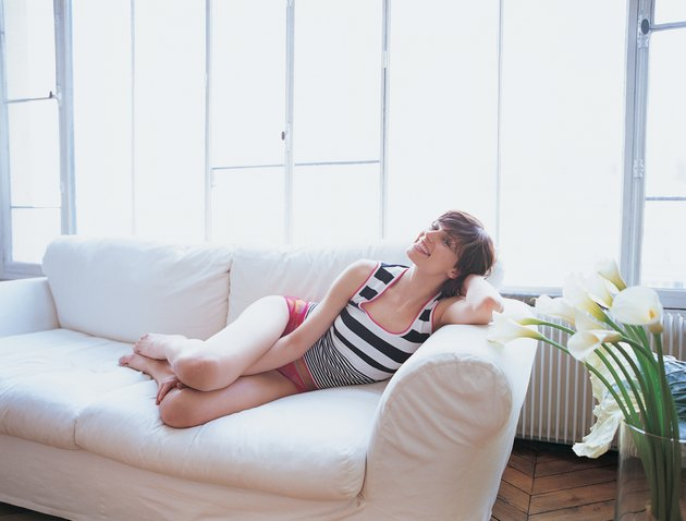Young Woman Lying on Sofa Smiling and Leaning on her Elbow