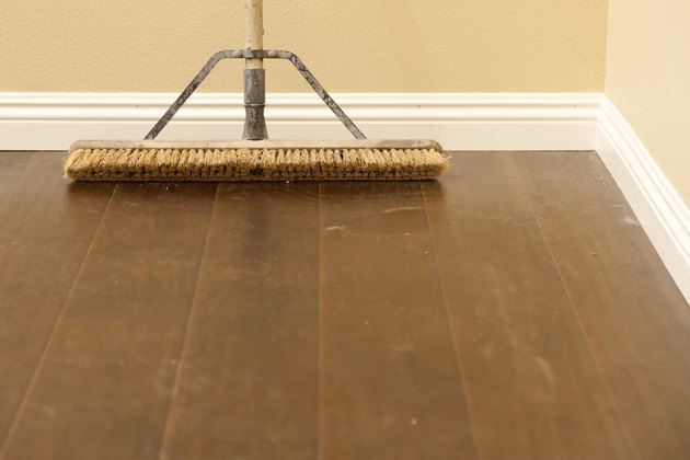 Push Broom on Newly Installed Dusty Laminate Floor and Baseboard
