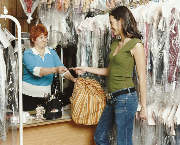 Shop Assistant Giving a Ticket to a Customer in a Dry Cleaners