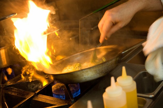 Chef cooking with a flaming pan.