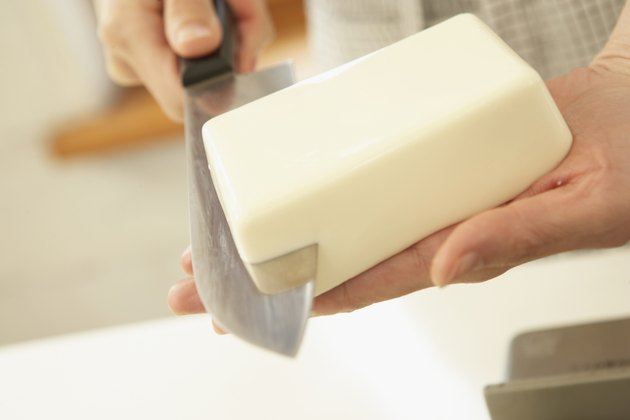 Woman cutting Tofu on hand, close up