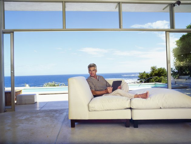 Mature Man Sitting on a Large Sofa in a Modern Room with the Sea in the Background
