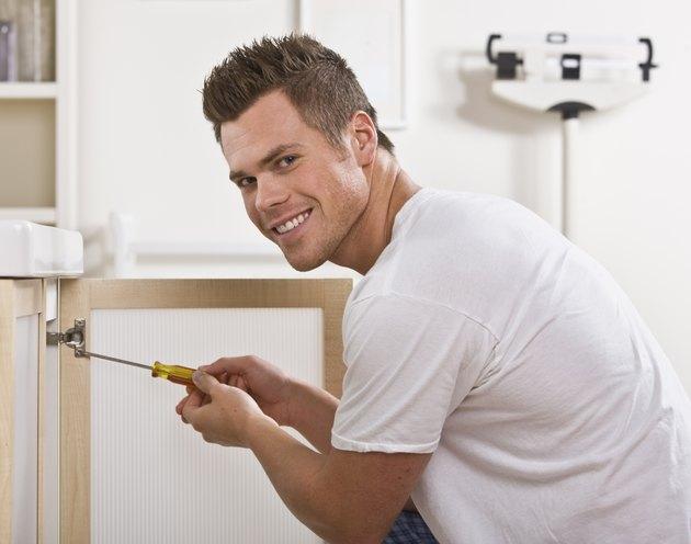 Smiling Man Fixing Cabinet Door