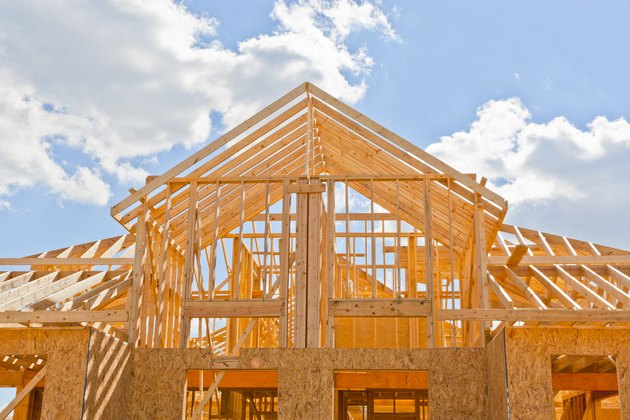New residential construction home framing against a blue sky