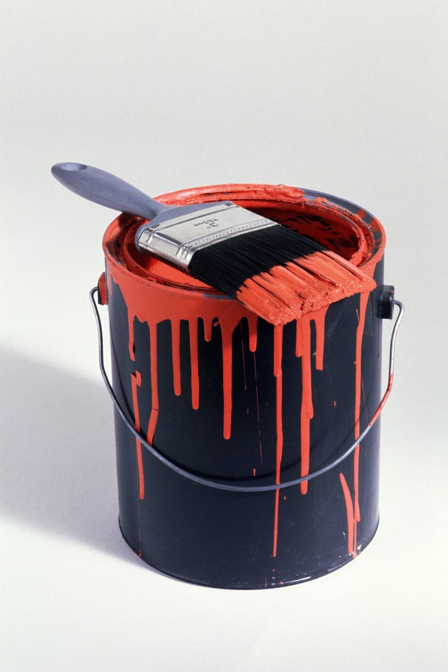 Can of red paint with brush