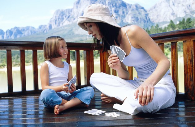 Mother and daughter playing cards on deck of cabin