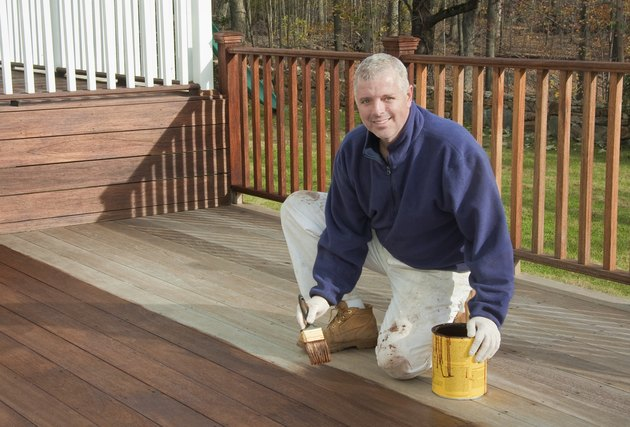 painter or handyman staining a deck