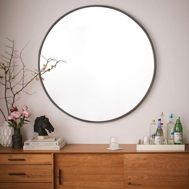 Oversized round mirror with thin dark metal border