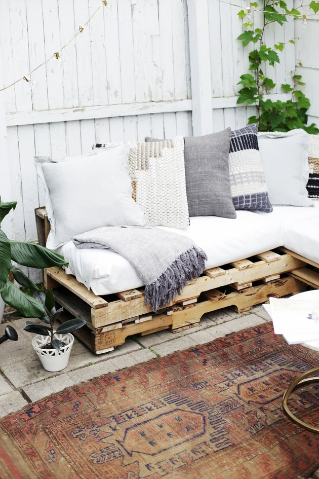 Wood pallet couch on patio with vintage rug.
