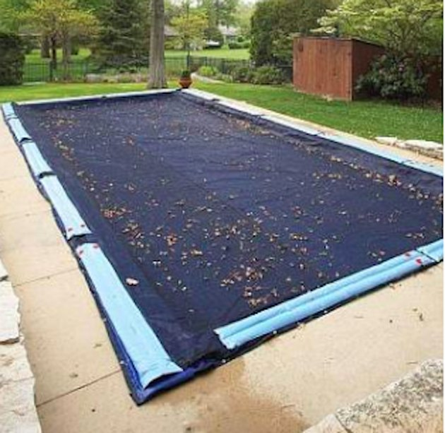 In-ground swimming pool with protective cover.