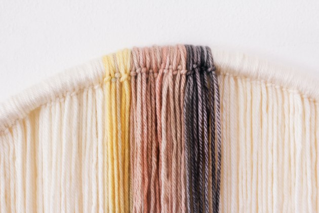 Tying dyed yarn strands onto hula hoop