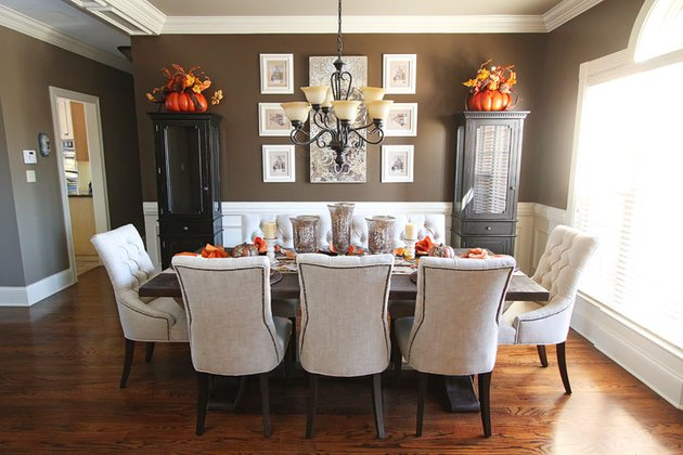 Brown walls and white wainscoting surrounding a dining table.