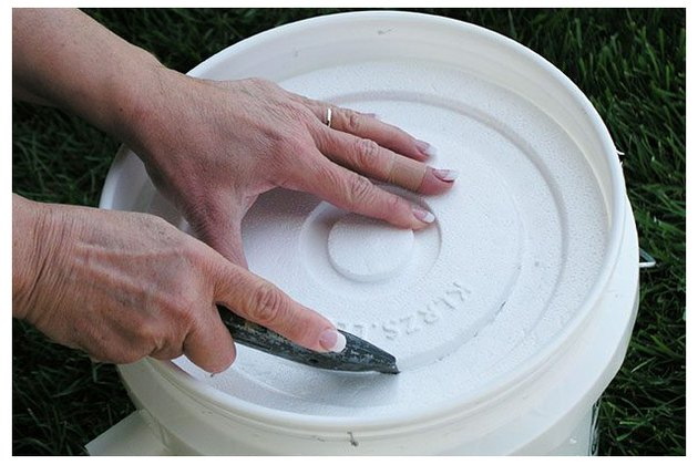 Cut a hole in the Styrofoam bucket lid.