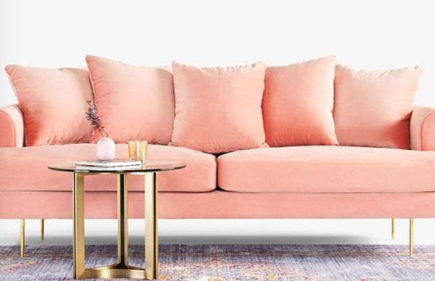 A blush-pink sofa in front of a round gold-legged side table.