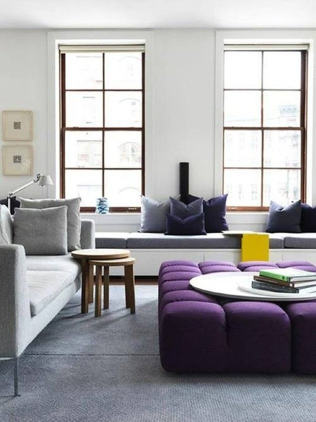 Purple tufted ottoman used as coffee table