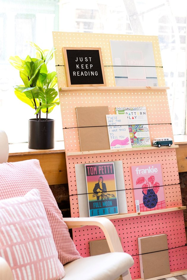 A pegboard bookcase that goes from pink to light orange